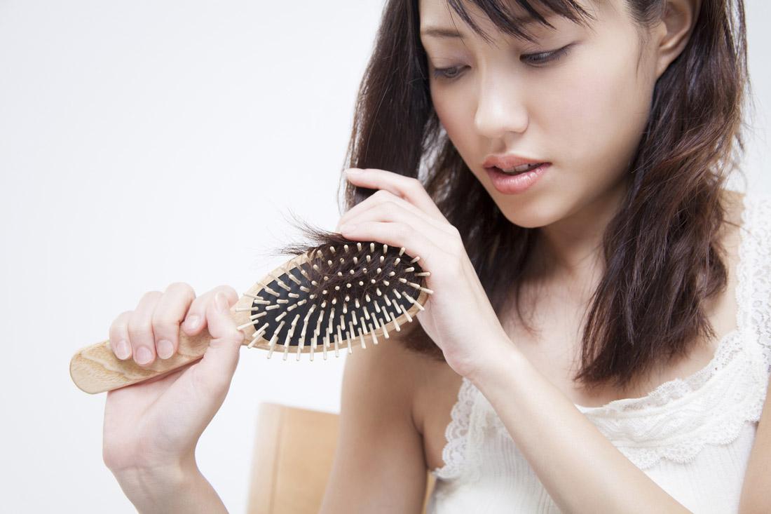 髪の毛をくしでとかす女性