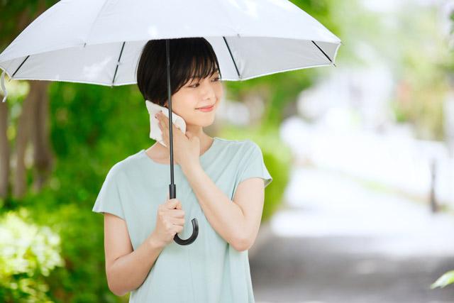 外で日傘を差している女性